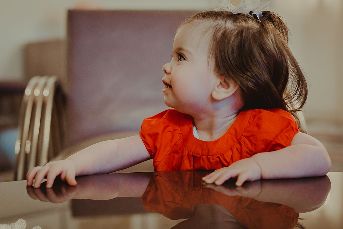 portrait of one year old daughter in red dress playing in living room of nyc apartment. photo by nyc family and newborn photographer Krystil McDowall