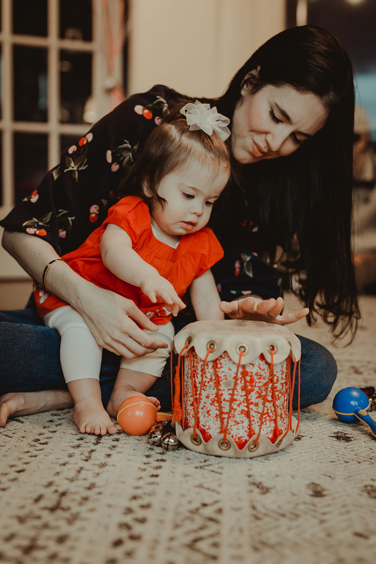 candid portrait of mom and her one year old daughter playing with a drum in nyc apartment. photo by nyc family and newborn photographer Krystil McDowall