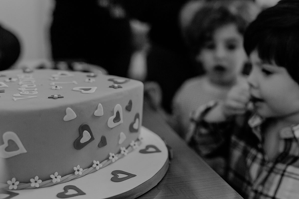 close up of boy looking at his sister's of one year birthday cake. photo by Krystil McDowall photography