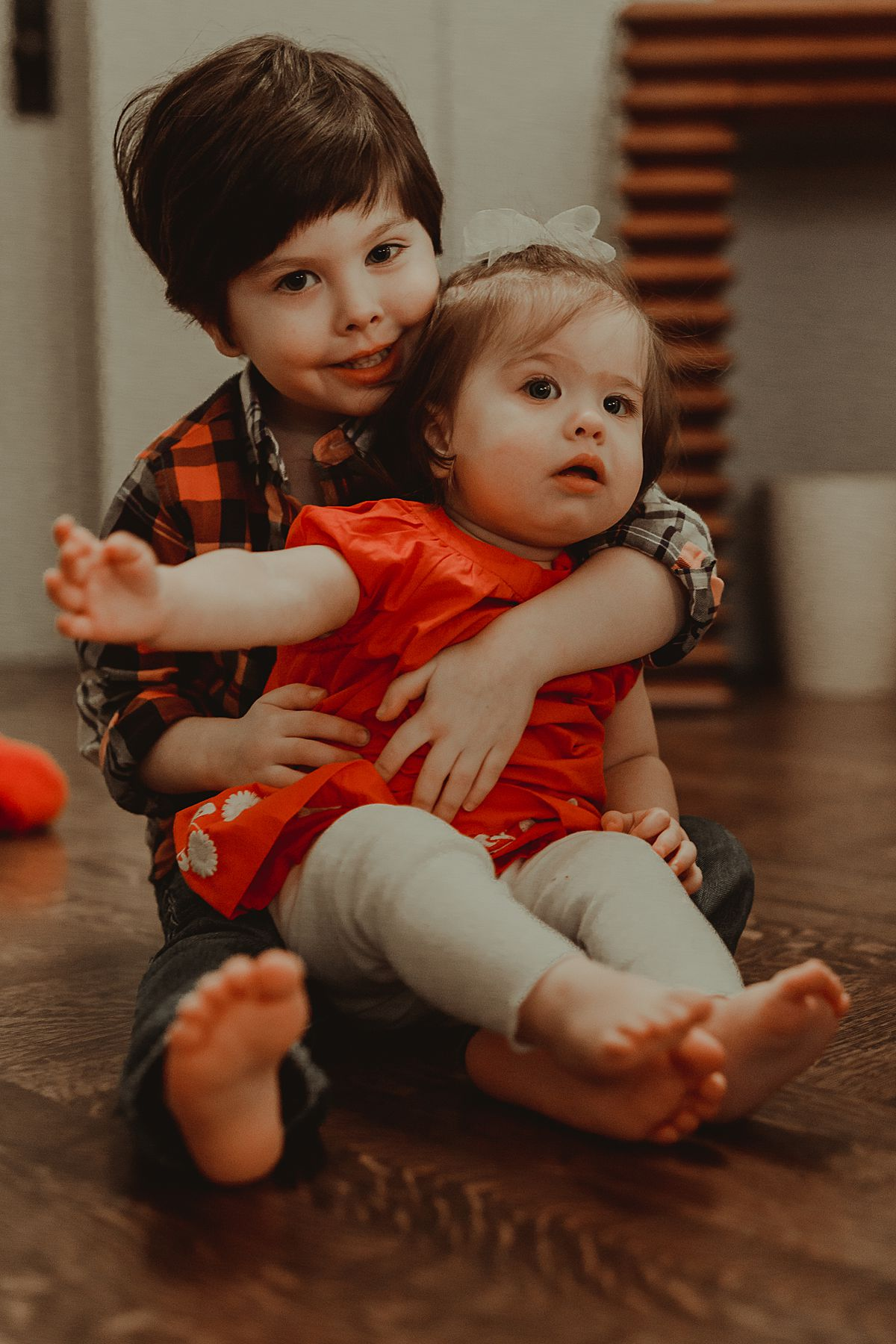 portrait of little sister sitting on big brother's lap. photo by nyc family and newborn photographer Krystil McDowall