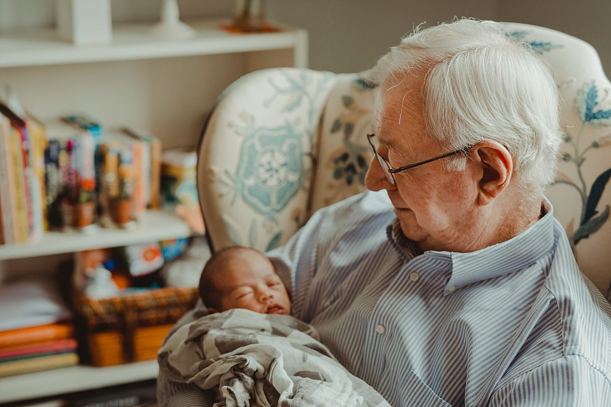 photo of grandad holding newborn in son during in home newborn session in nyc. photo by nyc family and newborn photographer krystil mcdowall