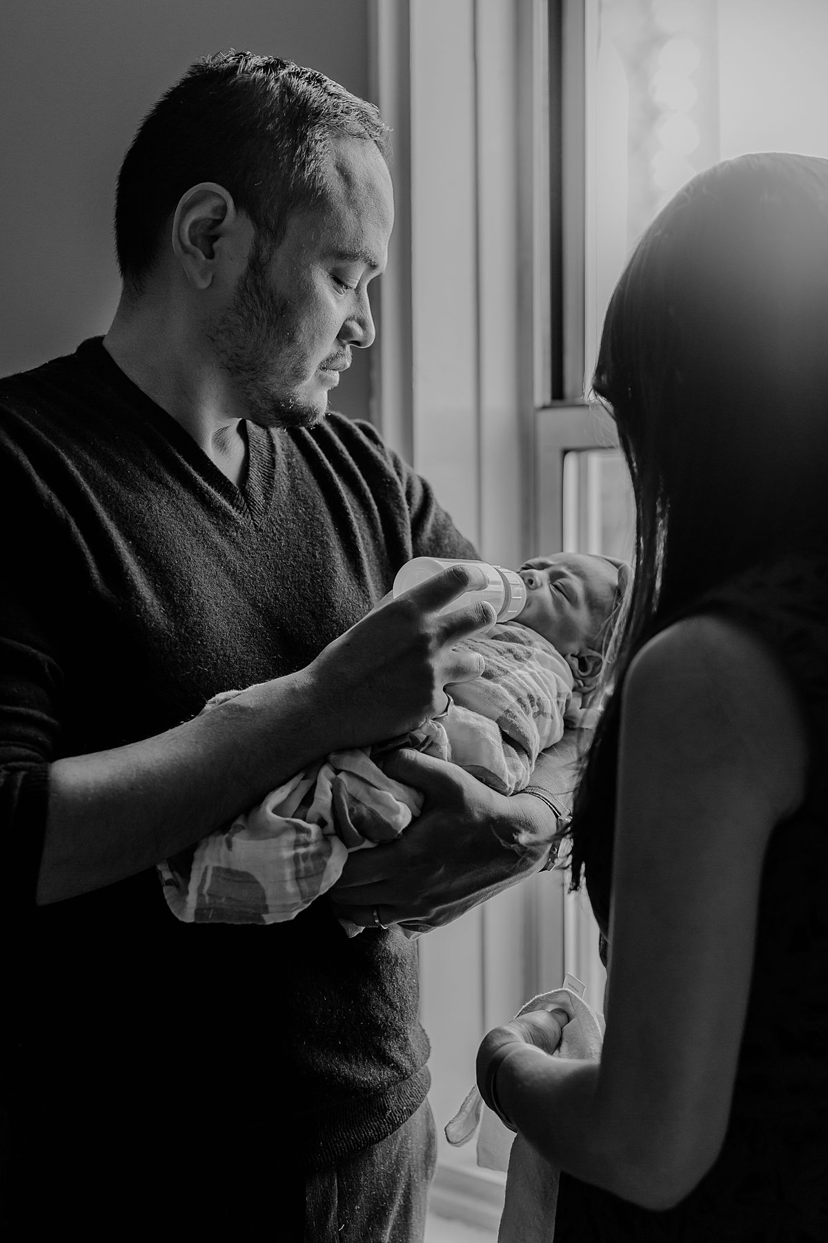 photo of mom and dad feeding newborn baby boy near light filled window of washington heights apartment. photo by nyc family and newborn photographer krystil mcdowall