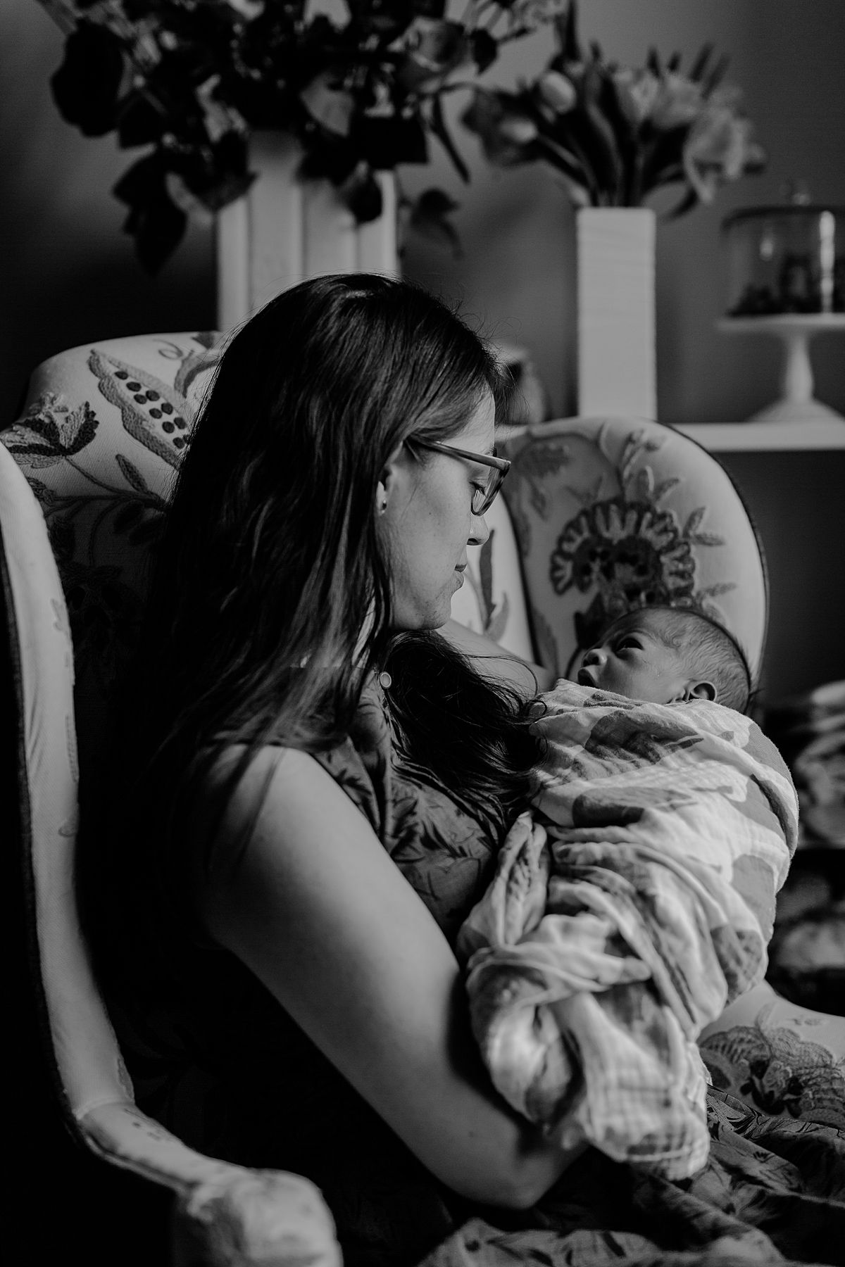 monochrome portrait of mom sitting in antique chair holding newborn son and dotingly looking at her son. photo by nyc family and newborn photographer krystil mcdowall