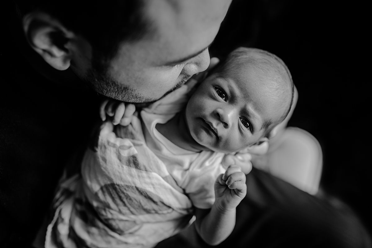 bird's eye photo of dad kissing newborn son who is wrapped in whale swaddle. photo by nyc family and newborn photographer krystil mcdowall