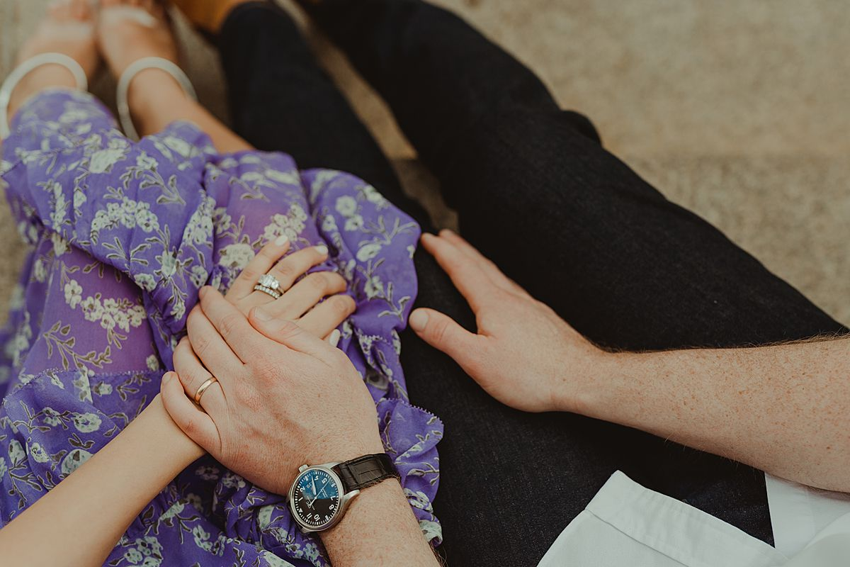 details shot of expecting couple that have interlocked hands resting on pregnant mom's beautiful purple and white flower dress.maternity photo by nyc family and newborn photographer krystil mcdowall