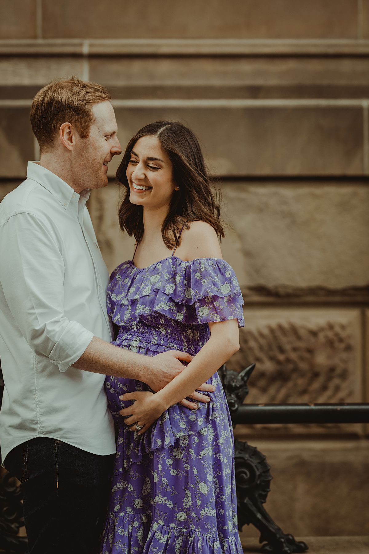 expecting couple standing and happily giggling in front of The Dakota or the Dakota Apartments on central park west nyc for maternity photo session. maternity photo by nyc family and newborn photographer krystil mcdowall