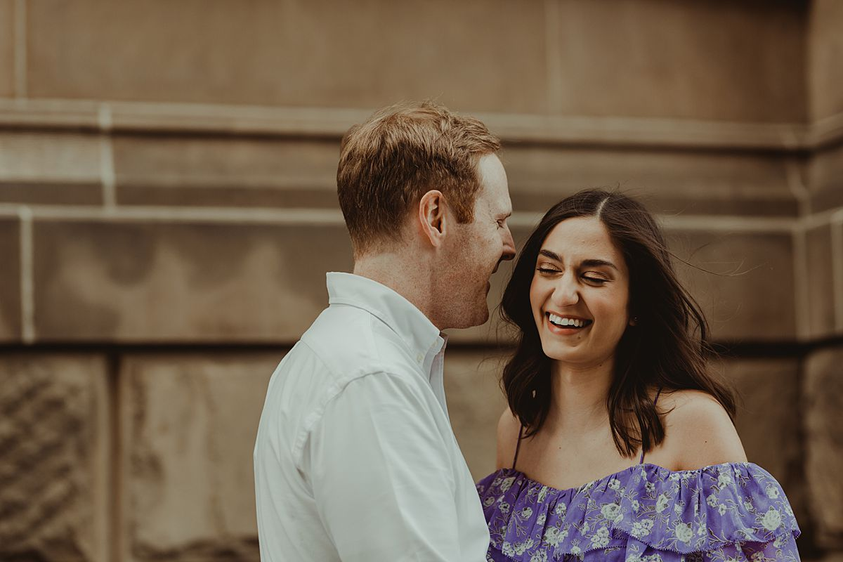 expecting couple happily giggling in front of The Dakota on central park west nyc during maternity photo session. maternity photo by nyc family and newborn photographer krystil mcdowall