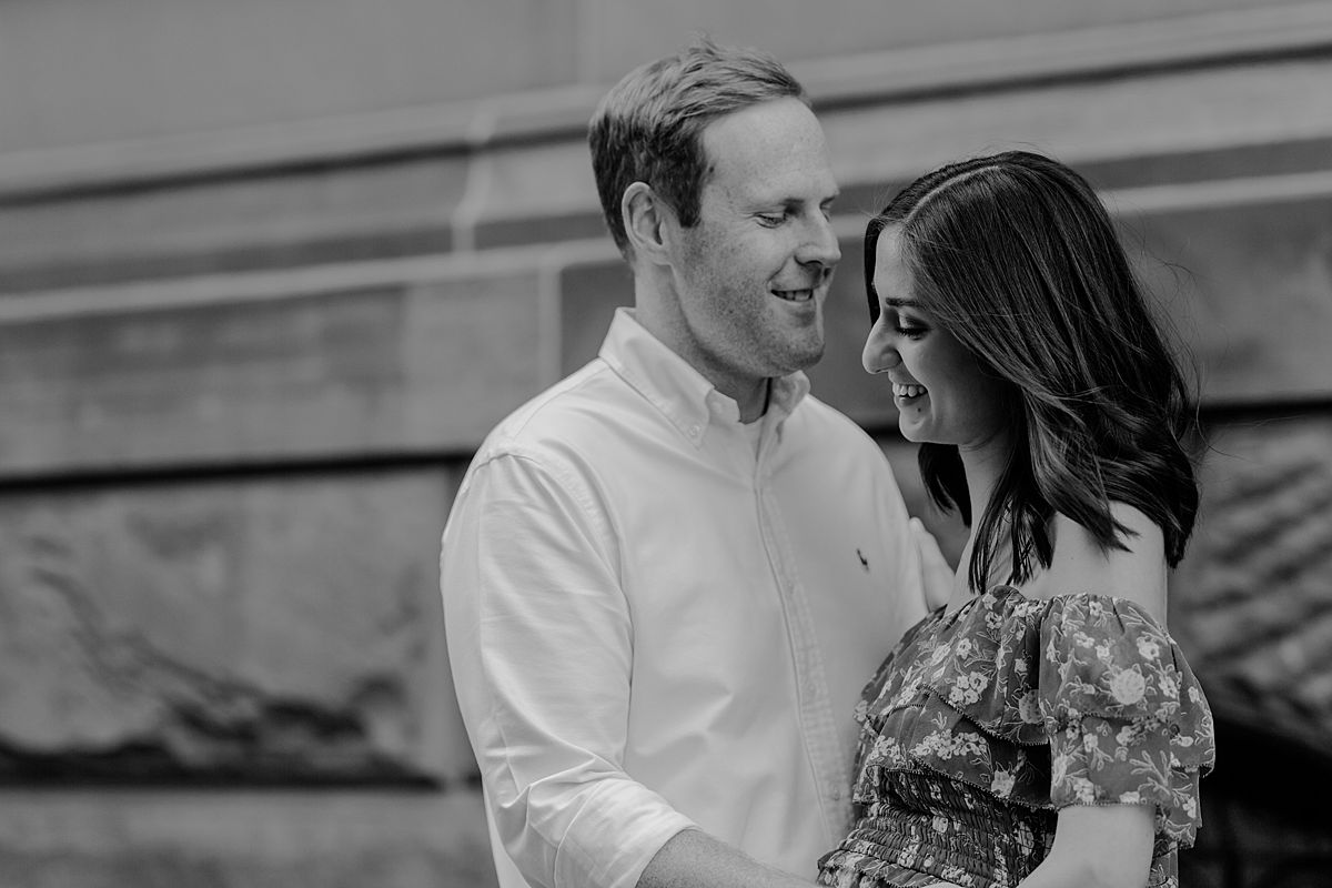 black and white portrait of expecting couple standing in front of The Dakota on central park west nyc for maternity photo session. maternity photo by nyc family and newborn photographer krystil mcdowall