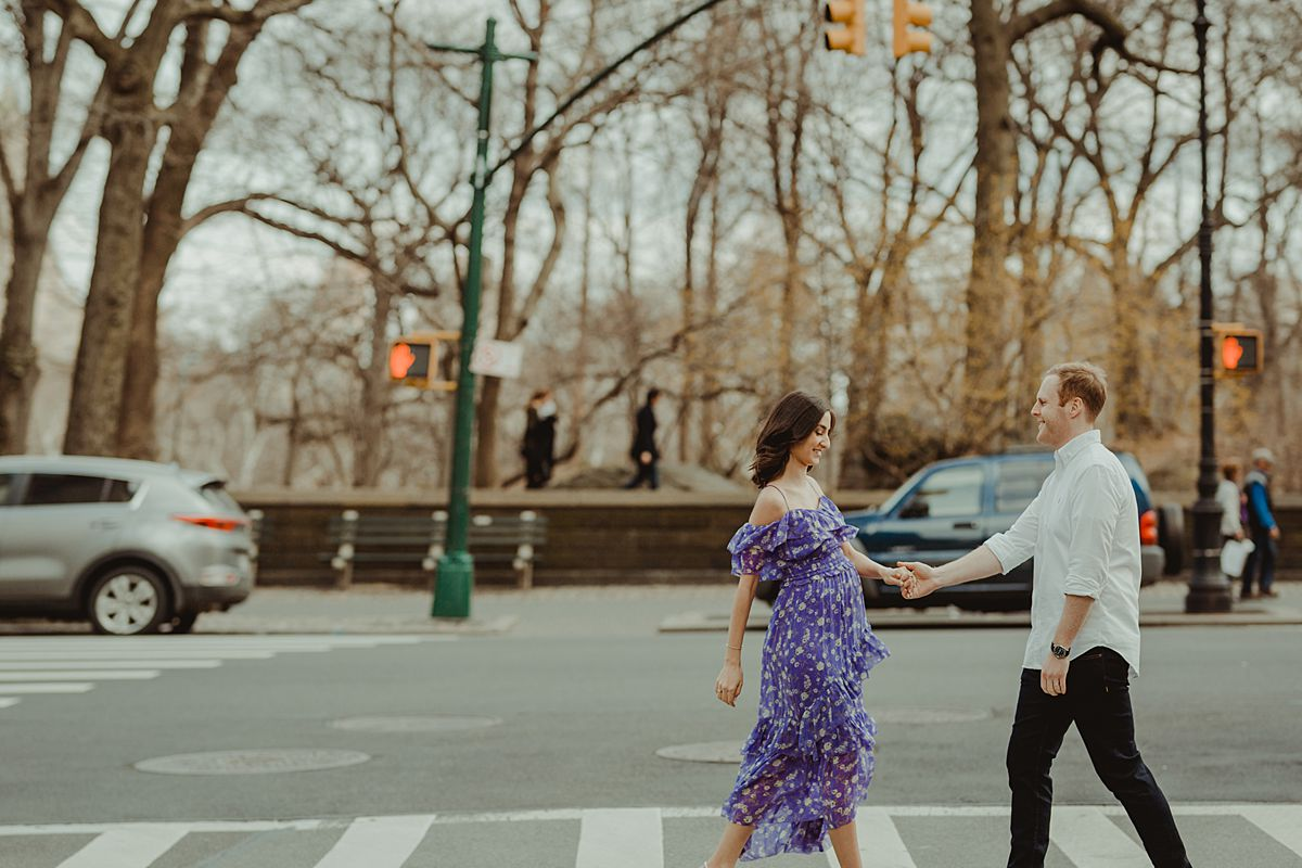 expecting couple walks along central park west with central park in the background for maternity photo session. maternity photo by nyc family and newborn photographer krystil mcdowall