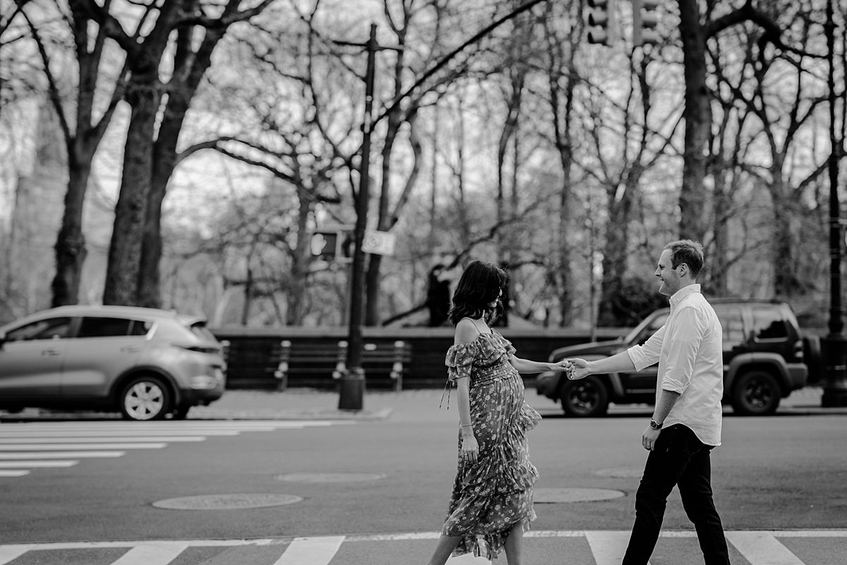 black and white lifestyle photo of expecting couple walking along central park west during their maternity photo session. image by nyc family and newborn photographer krystil mcdowall