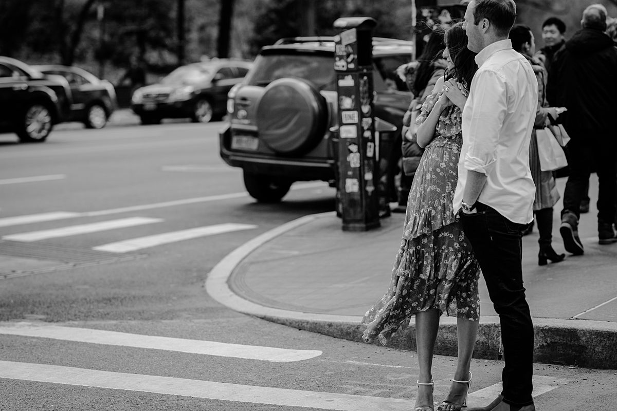 expecting couple stands on central park west people watching during maternity photo session. photo by nyc family and newborn photographer krystil mcdowall