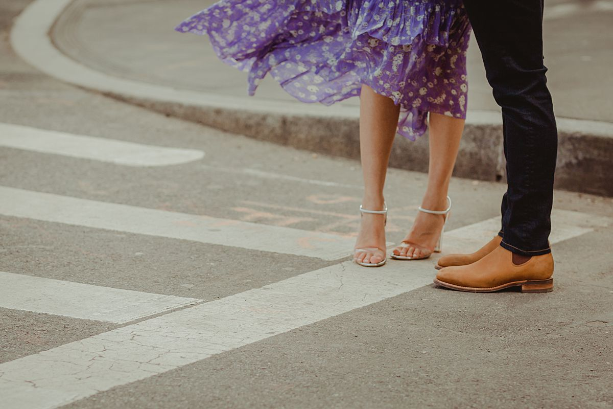 details shot of feet and footwear of expecting couple as they stand at pedestrian crossing on central park for maternity photo session. photo by nyc family and newborn photographer krystil mcdowall