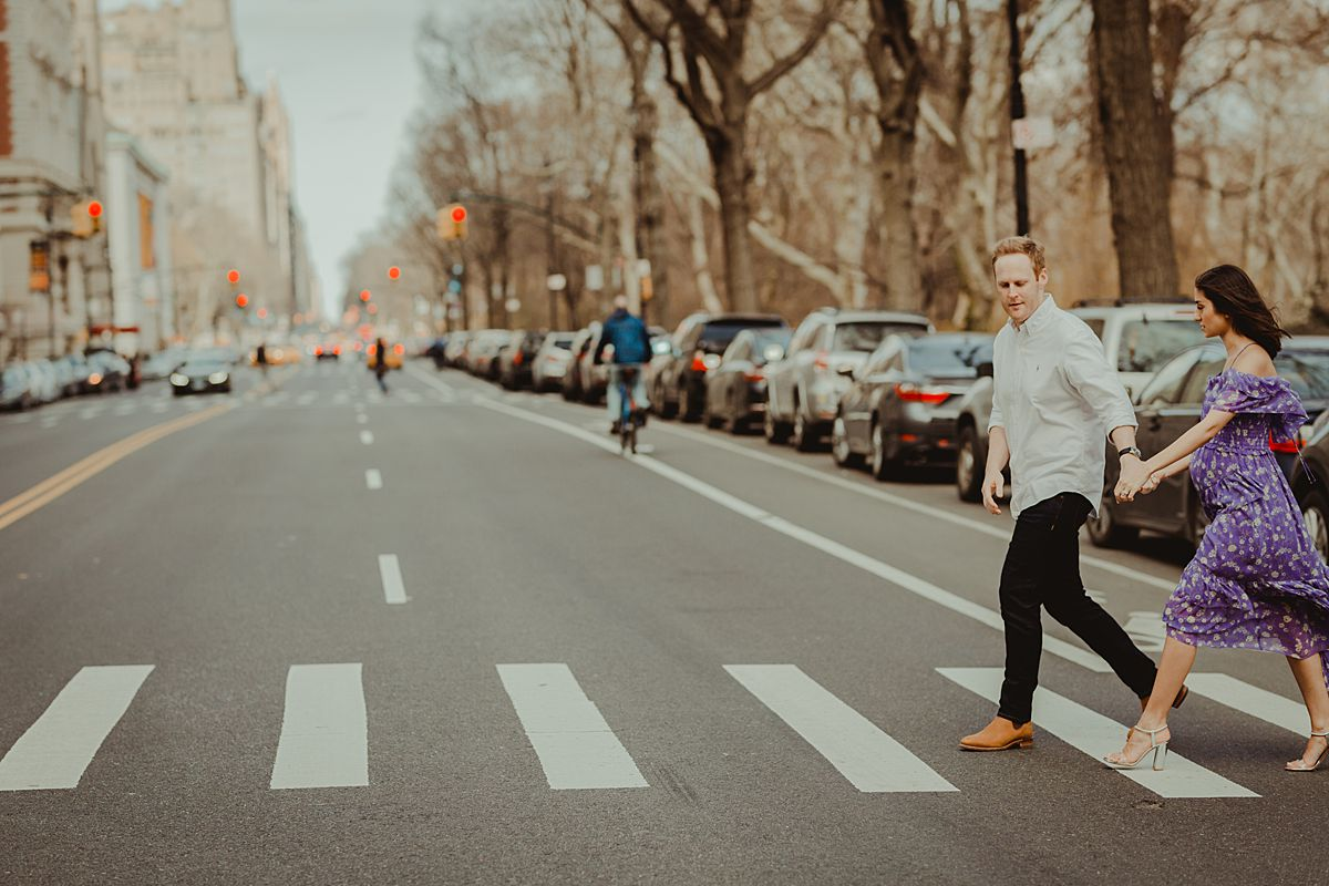 expecting couple walks along pedestrian crossing at 72nd street on central park west. maternity photo by nyc family and newborn photographer krystil mcdowall