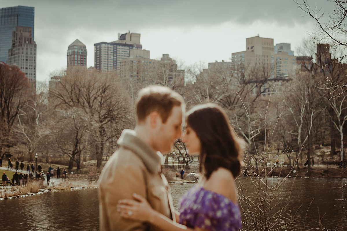 blurred portrait of expecting mom and dad embracing each other on the bow bridge during maternity photo session. photo by nyc family and newborn photographer krystil mcdowall