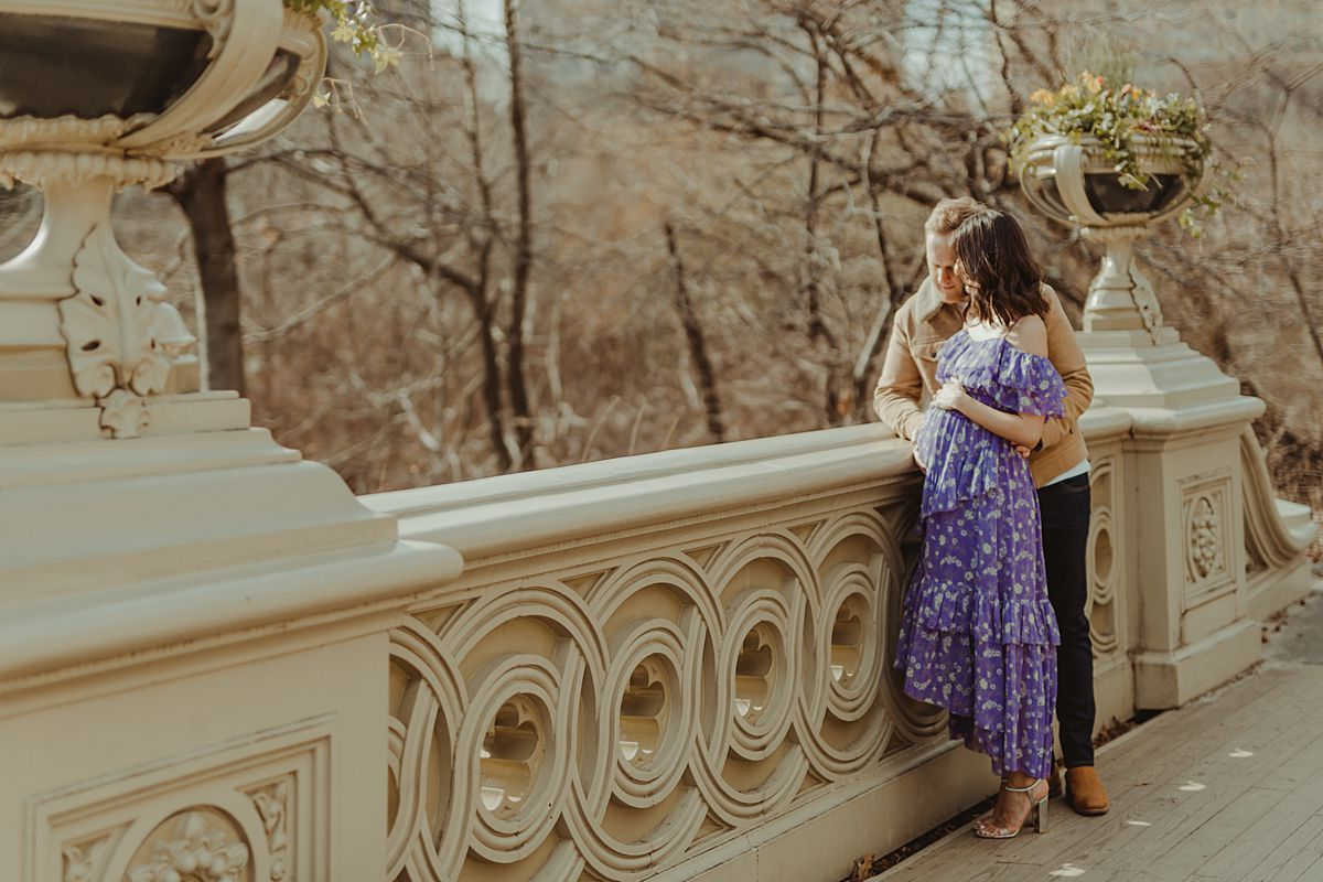 expecting couple stands on bow bridge in central park looking out at nyc skyline during maternity photo session. image by nyc family and newborn photographer krystil mcdowall