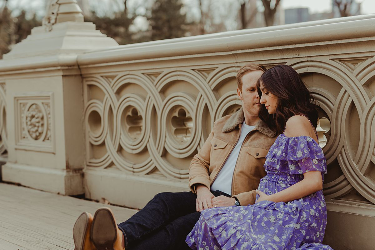 expecting couple sits on bow bridge in central park holding mama's expecting belly during maternity photo session. image by nyc family and newborn photographer krystil mcdowall