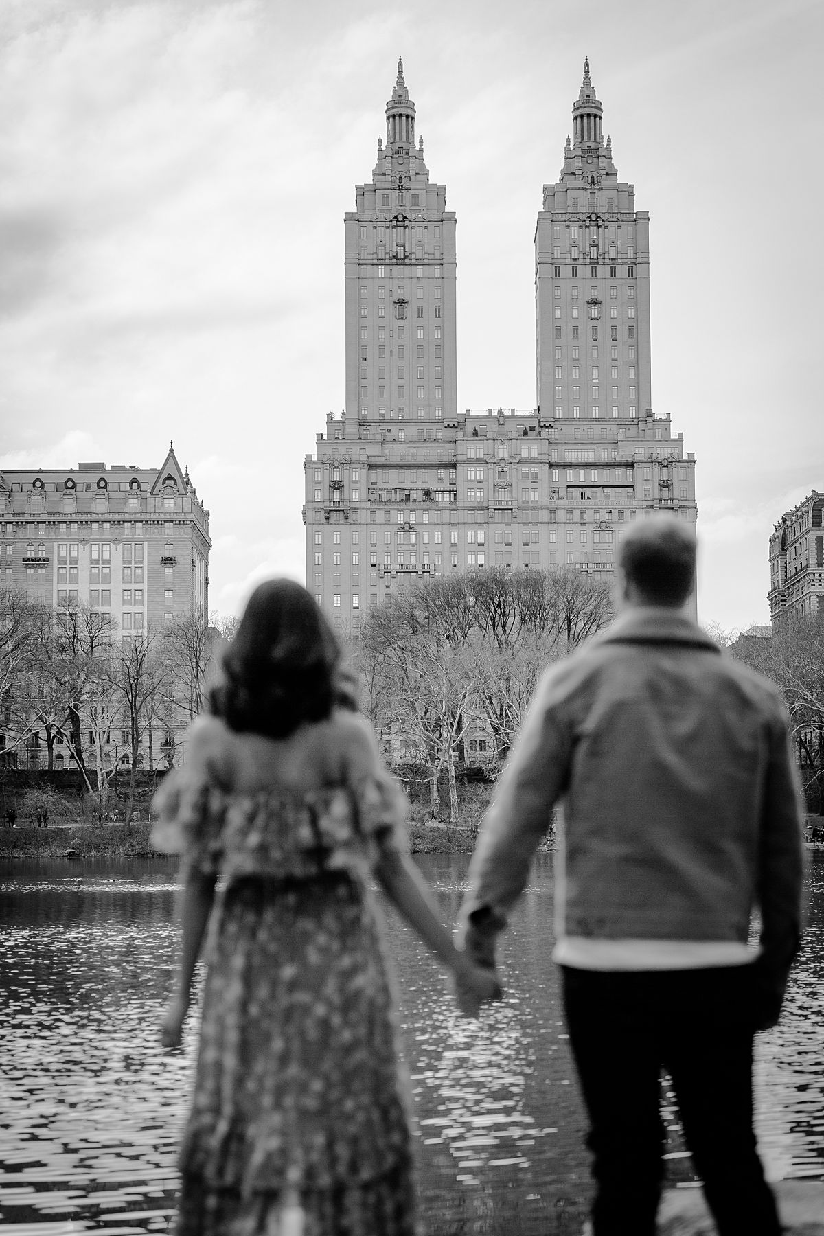 expecting stands in front of lake in central park looking at the san remo building during maternity photo session. image by nyc family and newborn photographer krystil mcdowall
