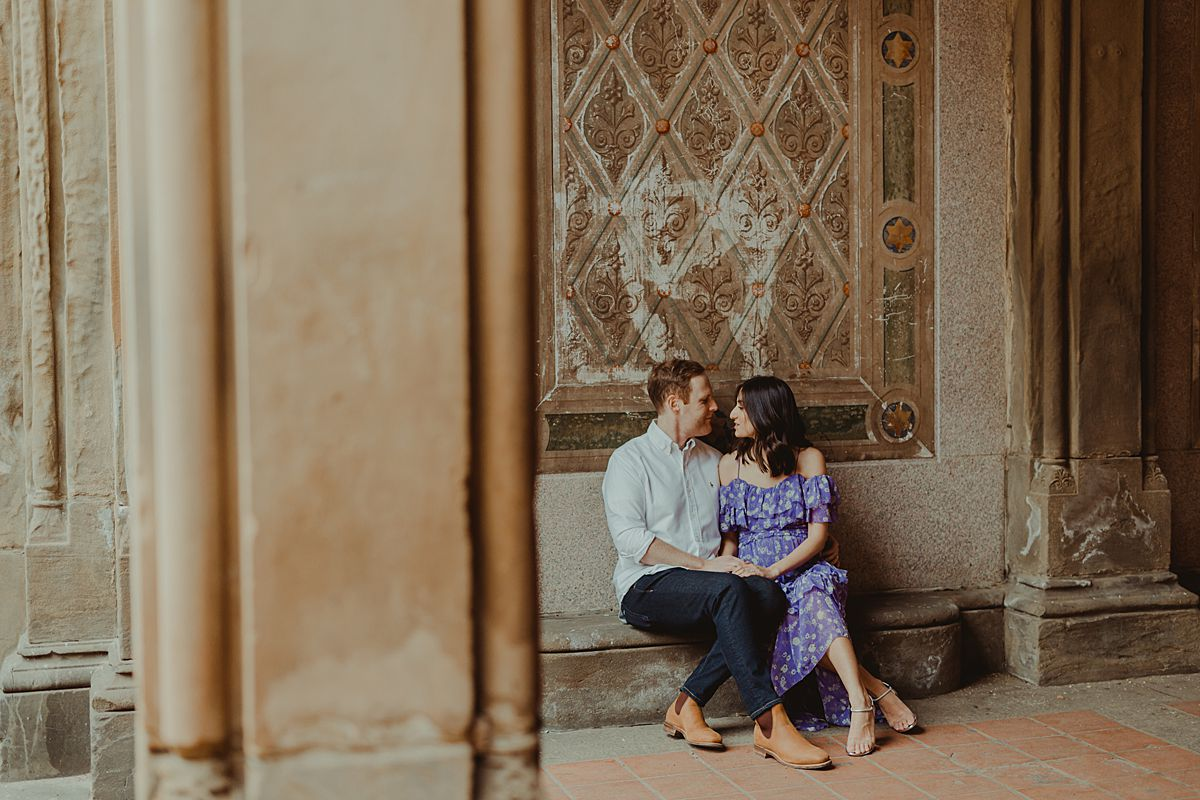 expecting couple sits at bethesda terrace in central park. image by nyc family and newborn photographer krystil mcdowall