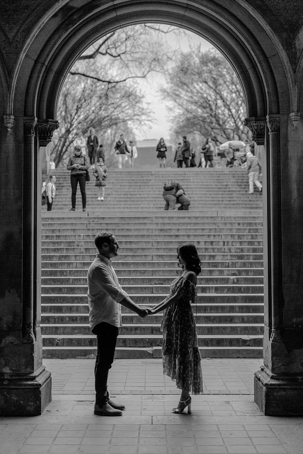 expecting couple stands at stairs at bethesda terrace in central park. image by nyc family and newborn photographer krystil mcdowall