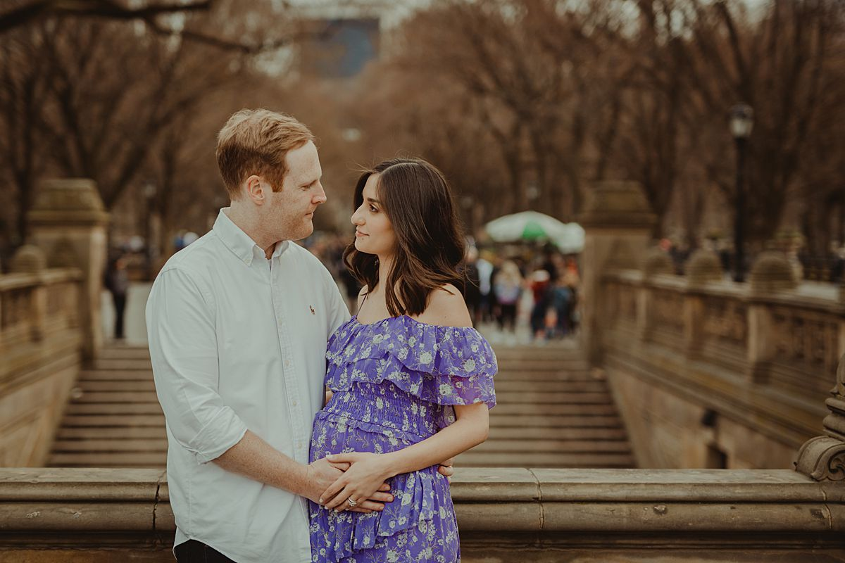 close up of expecting couple standing at bethesda terrace in central park new york city holding mom's expecting belly and looking lovingly at each other. image by nyc family and newborn photographer krystil mcdowall