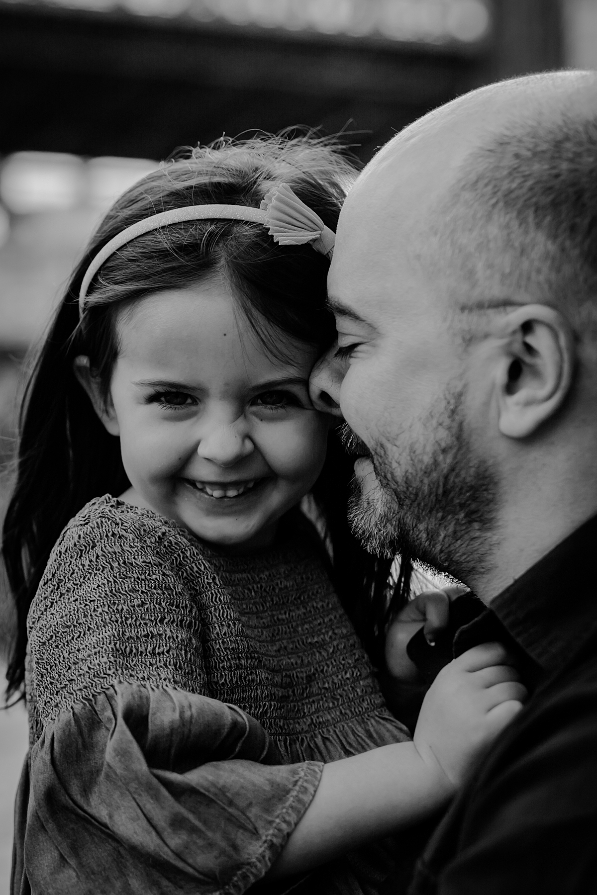 close up black and white portrait of dad and his daughter in front of the manhattan bridge in brooklyn. photo by nyc family and newborn photographer krystil mcdowall