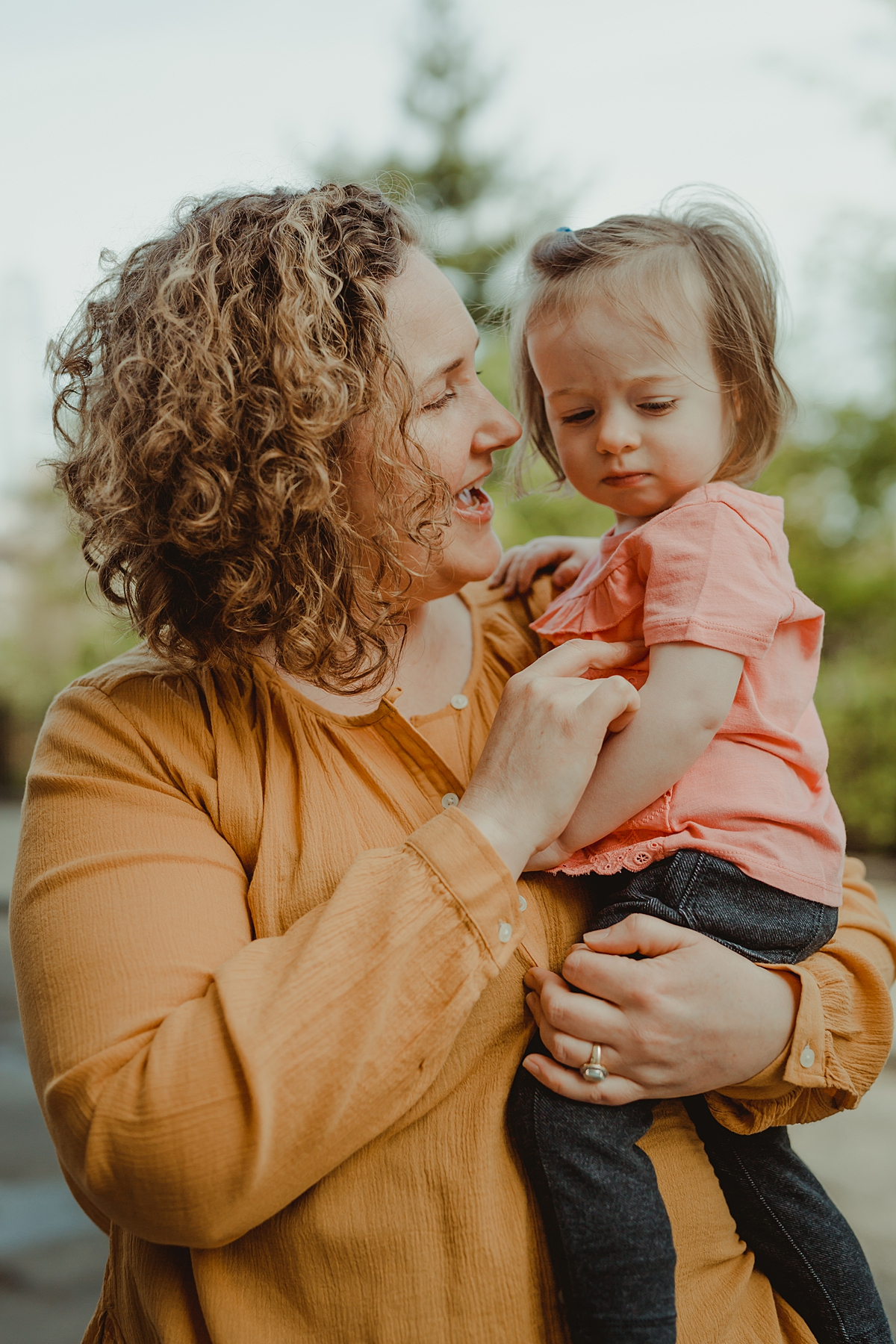 portrait of mom and daughter on cobble stoned street and bushes in dumbo brooklyn. photo by nyc family and newborn photographer krystil mcdowall