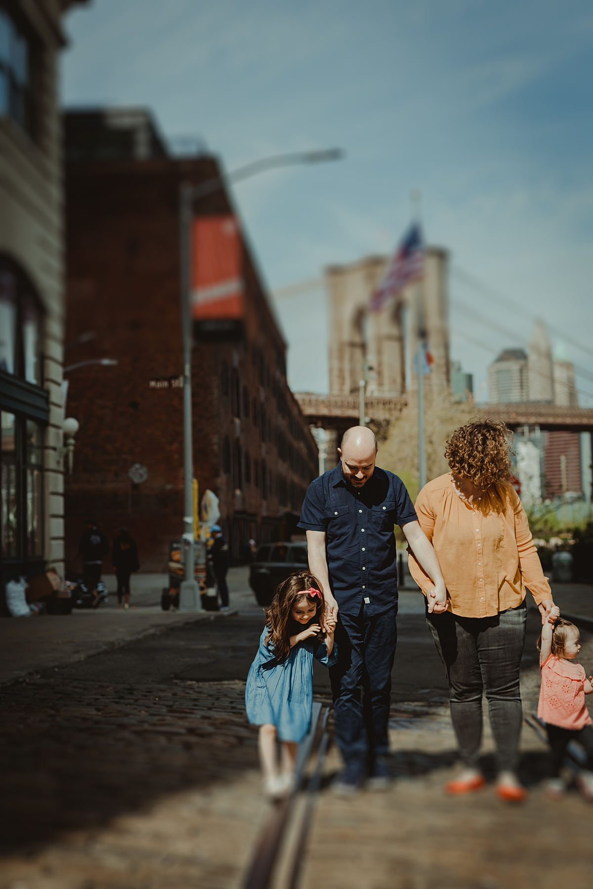 tilt shift candid family photo of family walking along cobble stoned street in dumbo brooklyn. photo by nyc family and newborn photographer krystil mcdowall