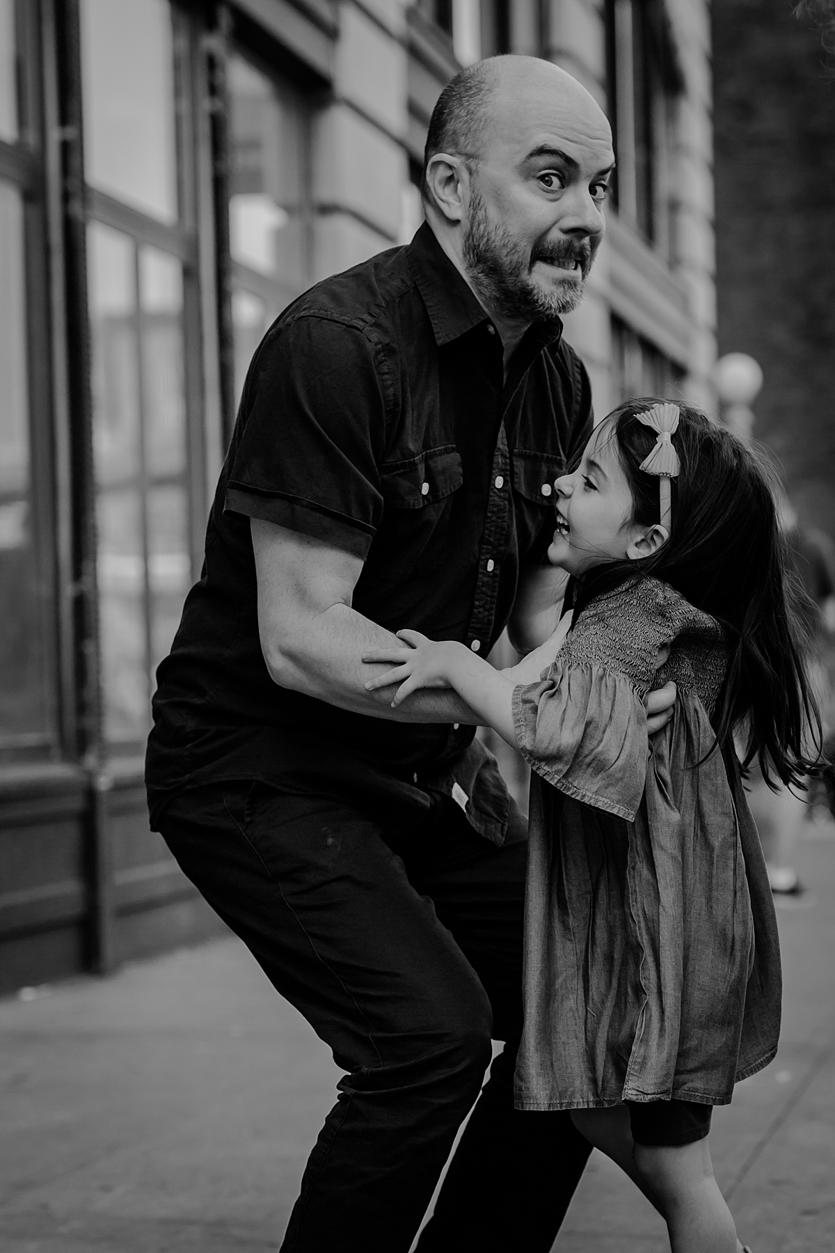 candid dad and daughter photo of dad pulling a funny face before he throws his daughter up in the air standing on dumbo brooklyn sidewalk. photo by nyc family and newborn photographer krystil mcdowall