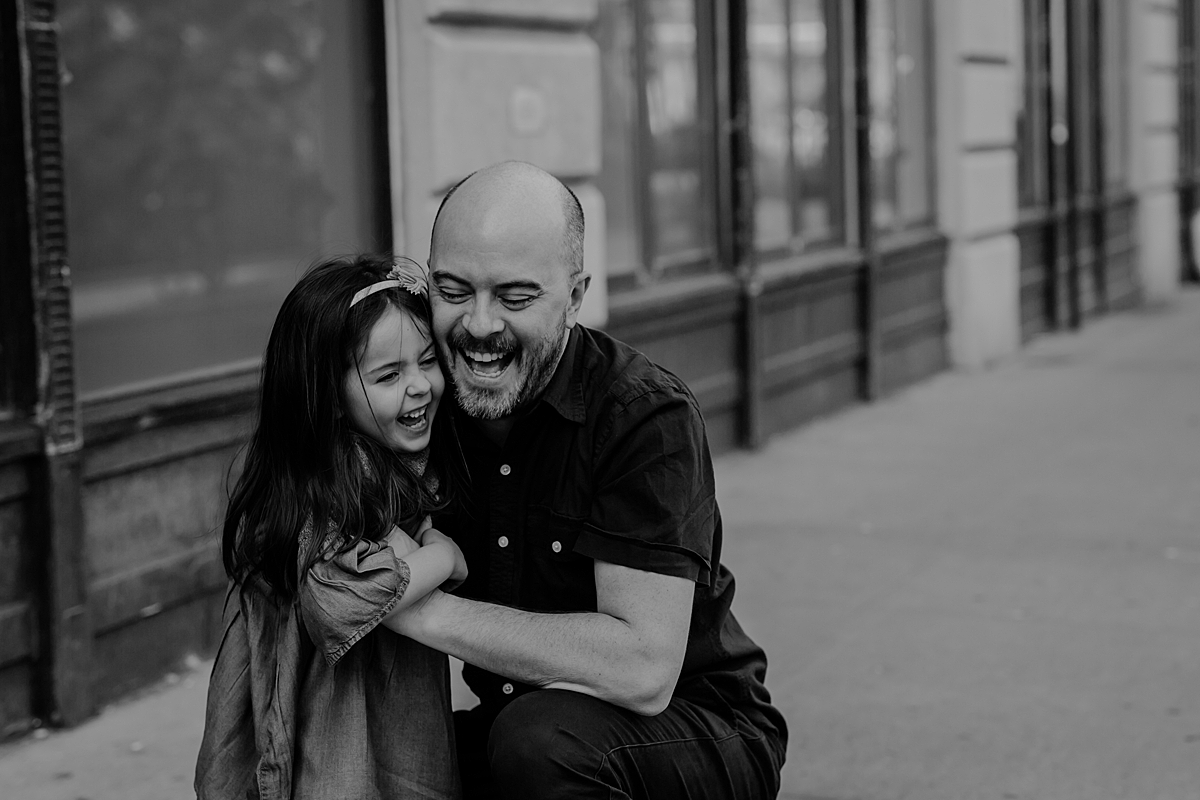 candid portrait of dad and daughter laughing together after dad threw daughter in the air. photo by krystil mcdowall photography