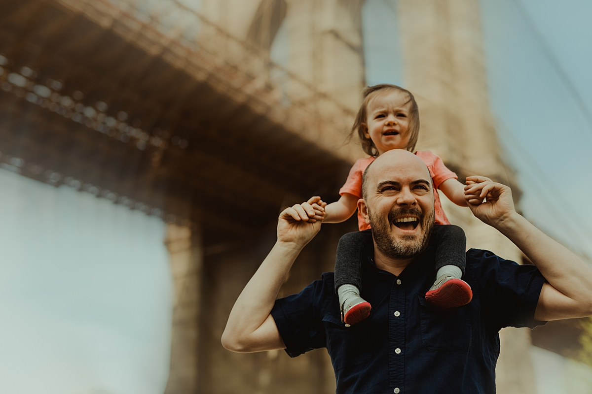 photo of dad giving young daughter a shoulder ride with blurred brooklyn bridge in the background. photo by nyc family and newborn photographer krystil mcdowall