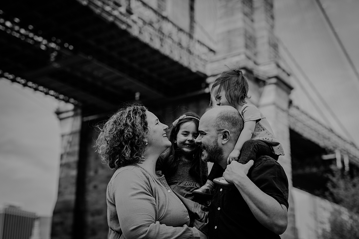 candid black and white family portrait of family standing in dumbo with brooklyn bridge as the backdrop. photo by nyc family and newborn photographer krystil mcdowall