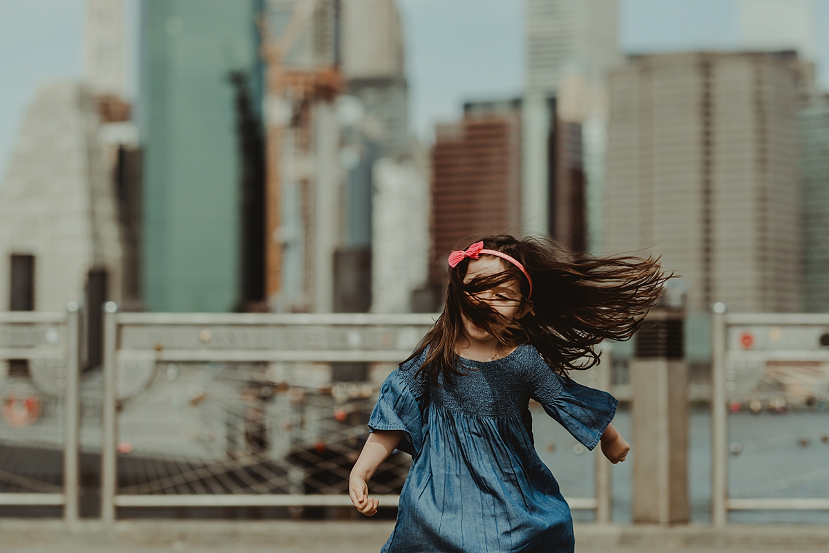 candid portrait of young daughter in blue dress playing at brooklyn bridge park in front of love locks with manhattan skyline in the background. photo by nyc family and newborn photographer krystil mcdowall