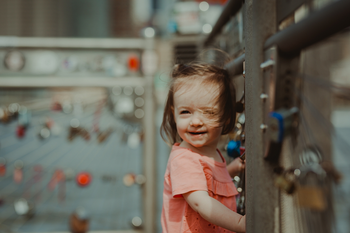 candid portrait of daughter in pink shirt standing in front of love locks with manhattan in the background. photo by nyc family and newborn photographer krystil mcdowall