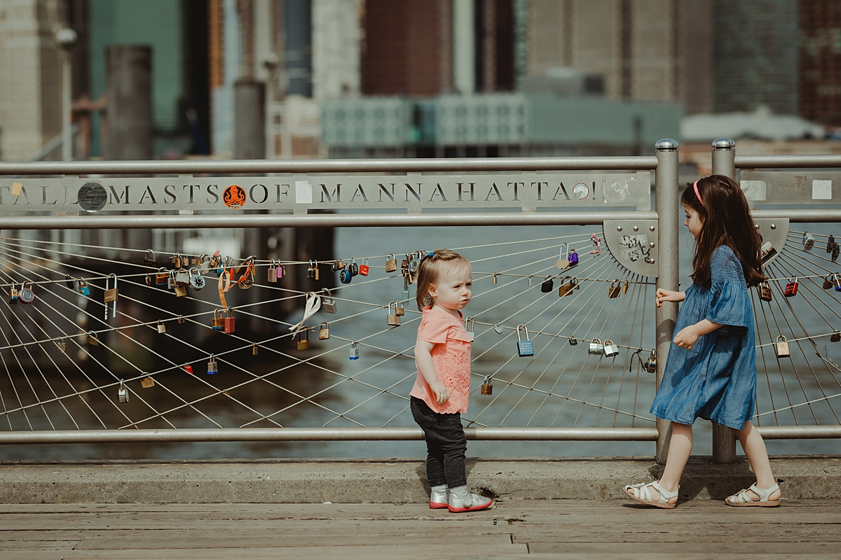 two daughters playing with the love locks at the brooklyn bridge park with manhattan skyline in the background. photo by nyc family and newborn photographer krystil mcdowall