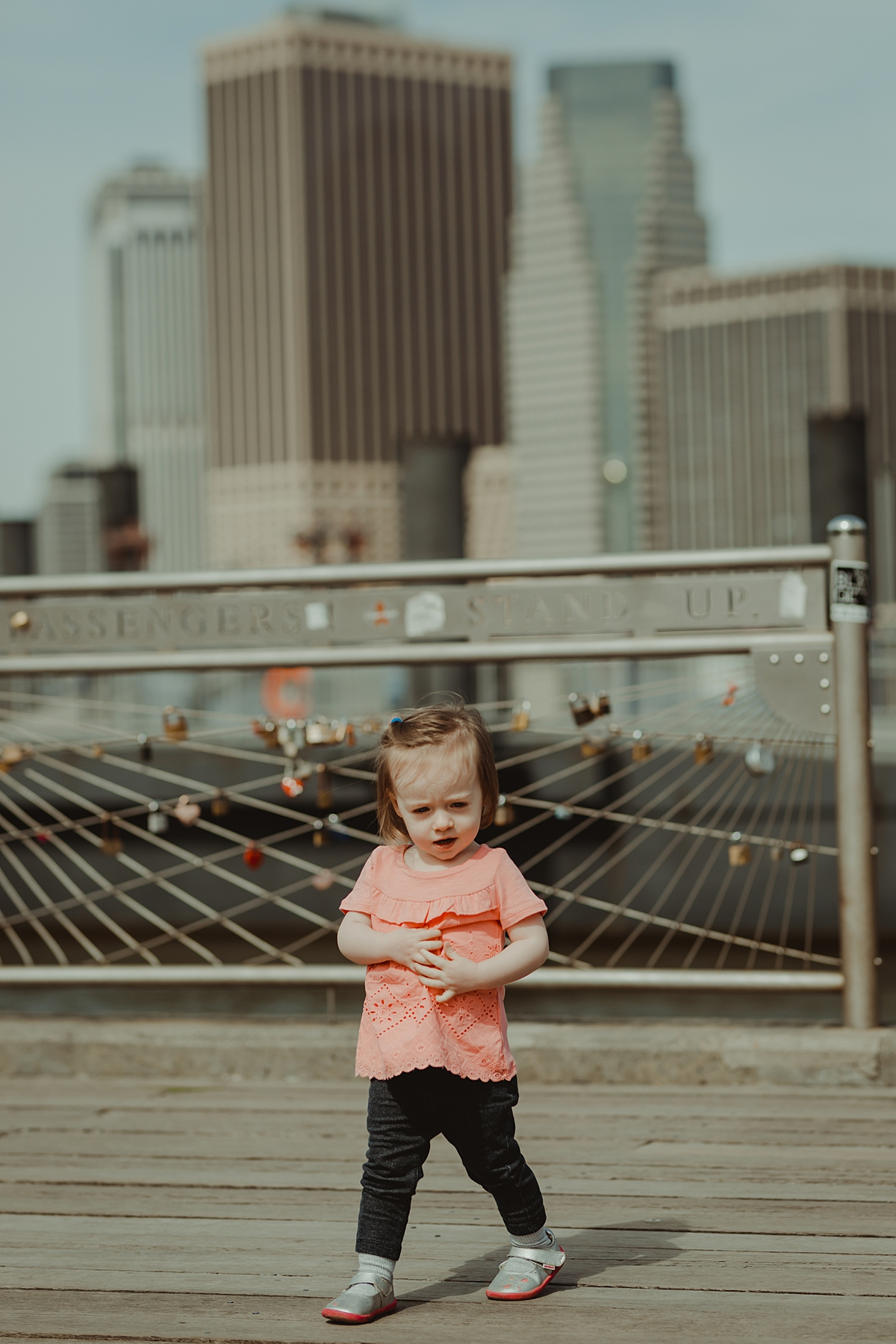 daughter playing at pier with the love locks and the manhattan skyline in the background. photo by nyc family and newborn photographer krystil mcdowall