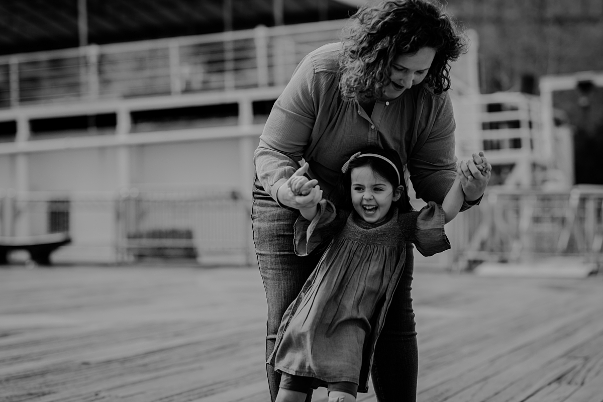 candid photo of mom and daughter after mom has spun daughter around at the brooklyn bridge park and daughter cannot stop laughing. photo by nyc family and newborn photographer krystil mcdowall