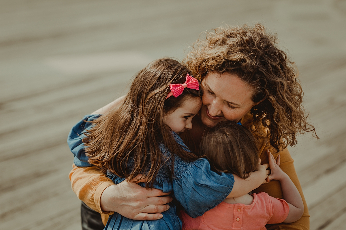 photo of mom hugging both her daughters at the pier at brooklyn bridge park. photo by nyc family and newborn photographer krystil mcdowall