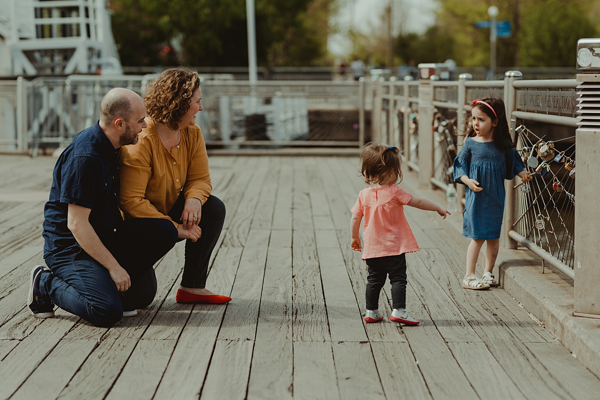 candid photo of family of four playing on the pier at brooklyn bridge park. photo by nyc family and newborn photographer krystil mcdowall