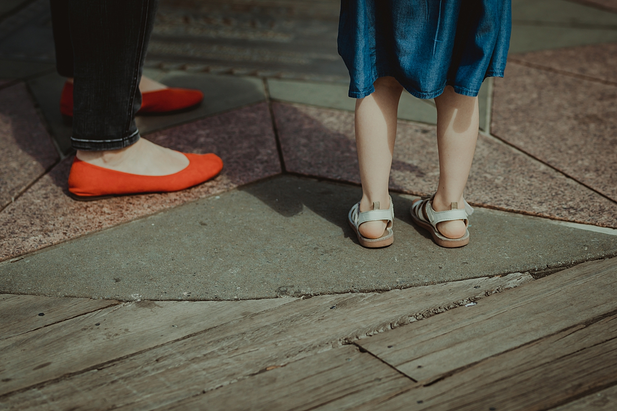 detail photo of mom's bright red flats and daughter's white buckle up shoes taken while standing at the pier at brooklyn bridge park. photo by nyc family and newborn photographer krystil mcdowall