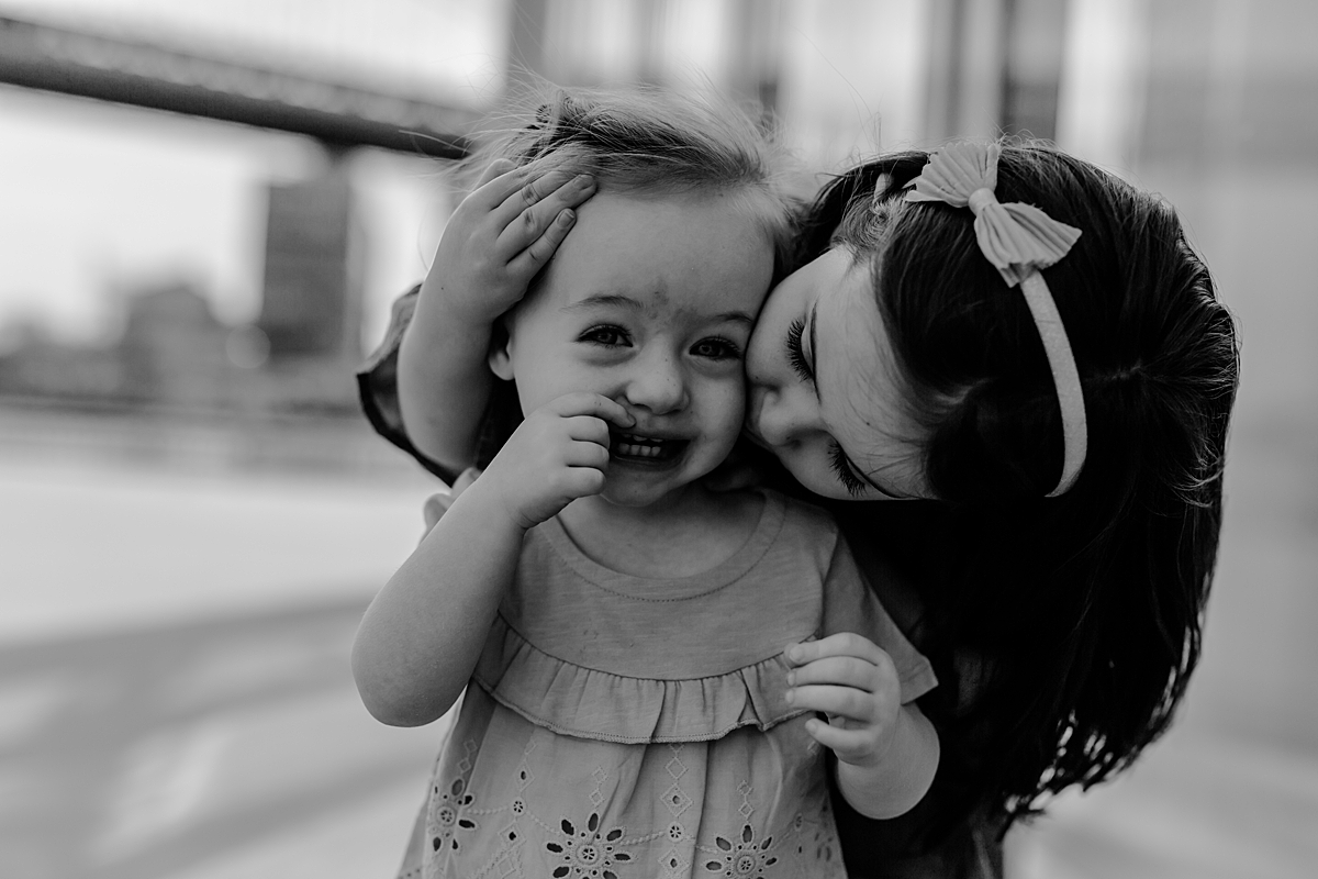 photo of big sister giving little sister a kiss on the cheek in front of jane's carousel in dumbo brooklyn. photo by nyc family and newborn photographer krystil mcdowall