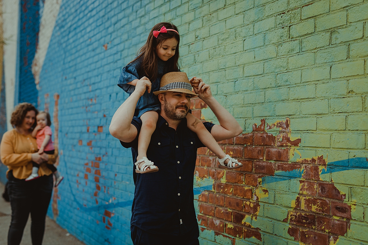 photo of family strolling in front of bright and colorful graffiti wall in dumbo brooklyn.photo by nyc family and newborn photographer krystil mcdowall