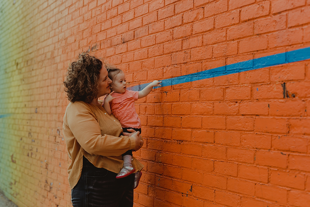 photo of mom and youngest daughter standing in front of bright orange graffiti wall in dumbo brooklyn.photo by nyc family and newborn photographer krystil mcdowall