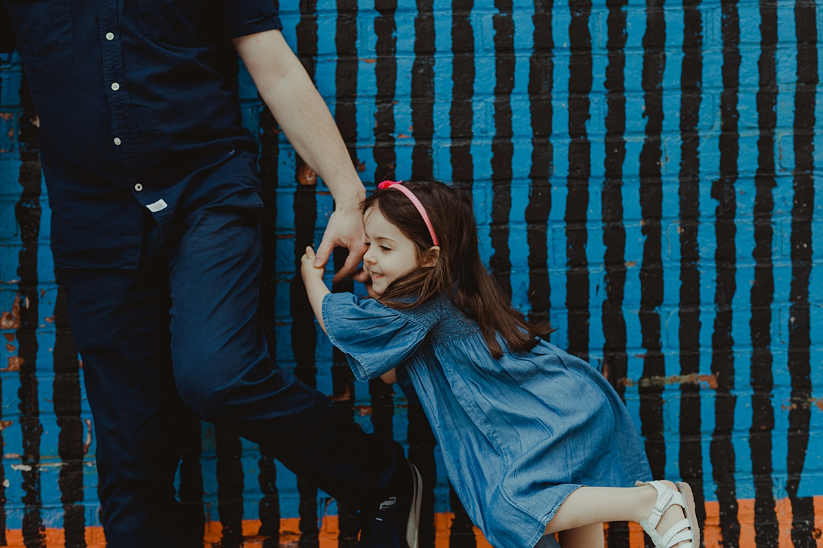 photo of daughter holding dad's hand and standing in front of bright blue and black graffiti wall in dumbo brooklyn.photo by nyc family and newborn photographer krystil mcdowall