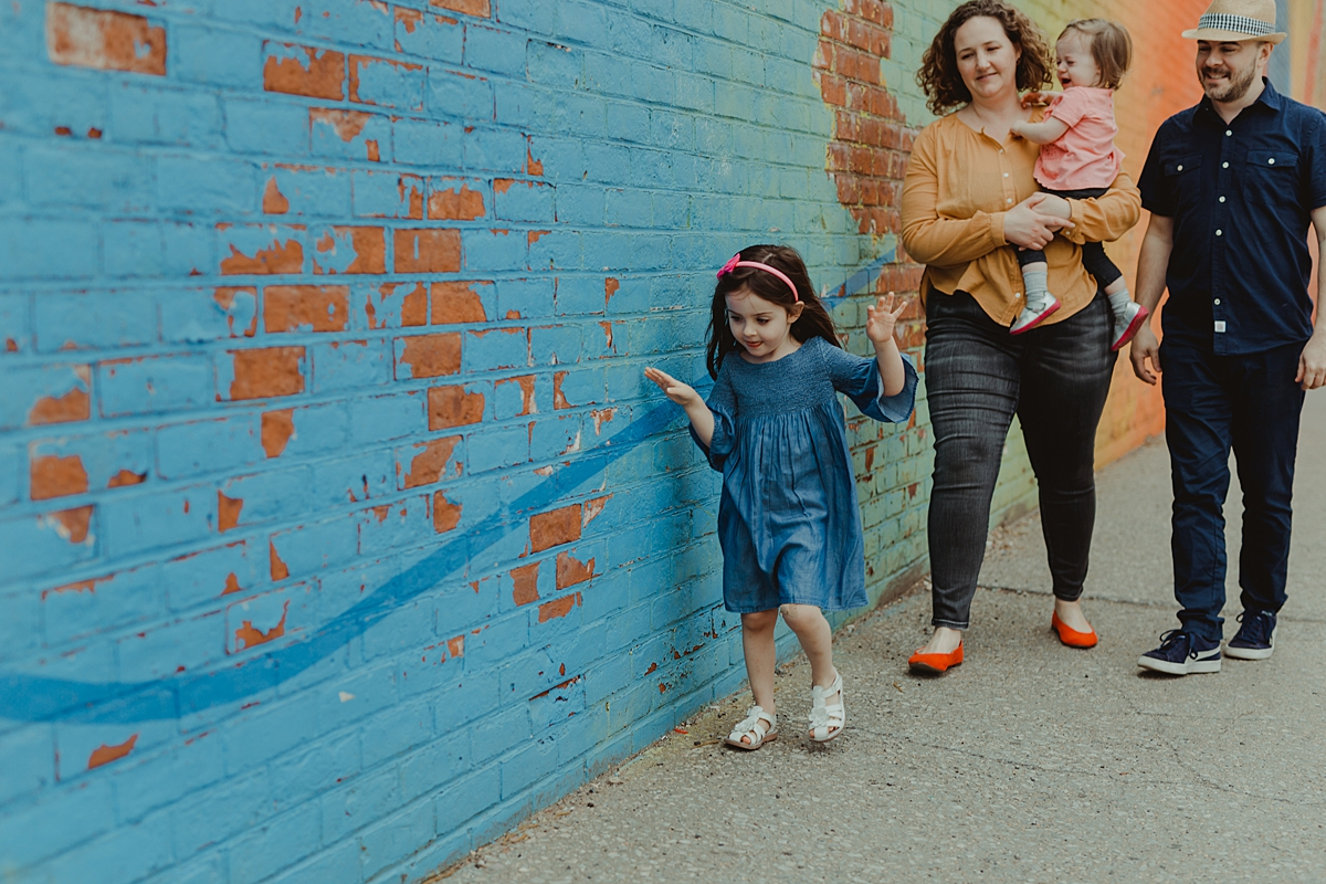 photo of family strolling in front of colorful graffiti wall during fun filled family photo session in new york city.photo by nyc family and newborn photographer krystil mcdowall