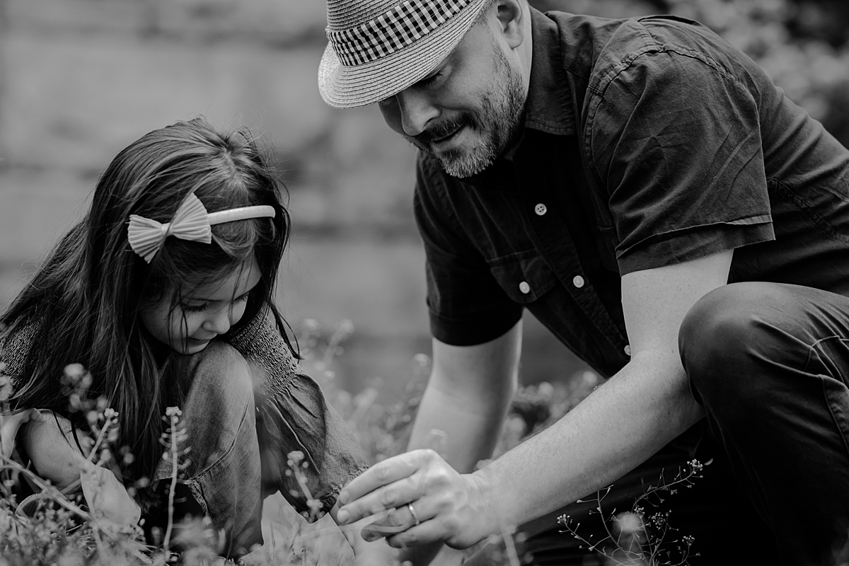 black and white portrait of young girl and her dad picking dandelions during family photo session in new york city.photo by nyc family and newborn photographer krystil mcdowall