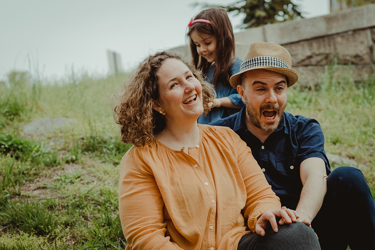 candid photo of young girl and mom and dad sitting on green grass amidst blooming cherry blossoms in brooklyn.photo by nyc family and newborn photographer krystil mcdowall
