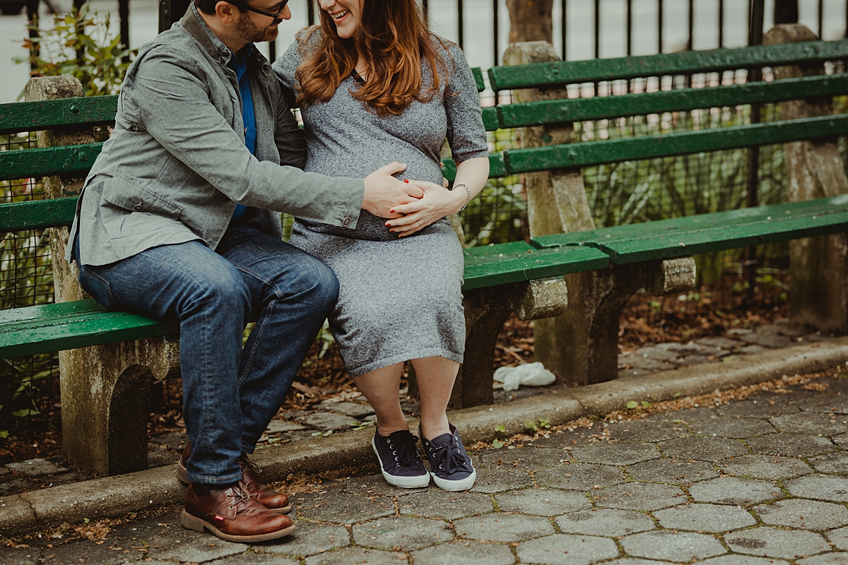 portrait of expecting mom and dad sitting on park bench in stuyvesant square with an emphasis on mom's pregnant belly. photo by nyc family and newborn photographer krystil mcdowall
