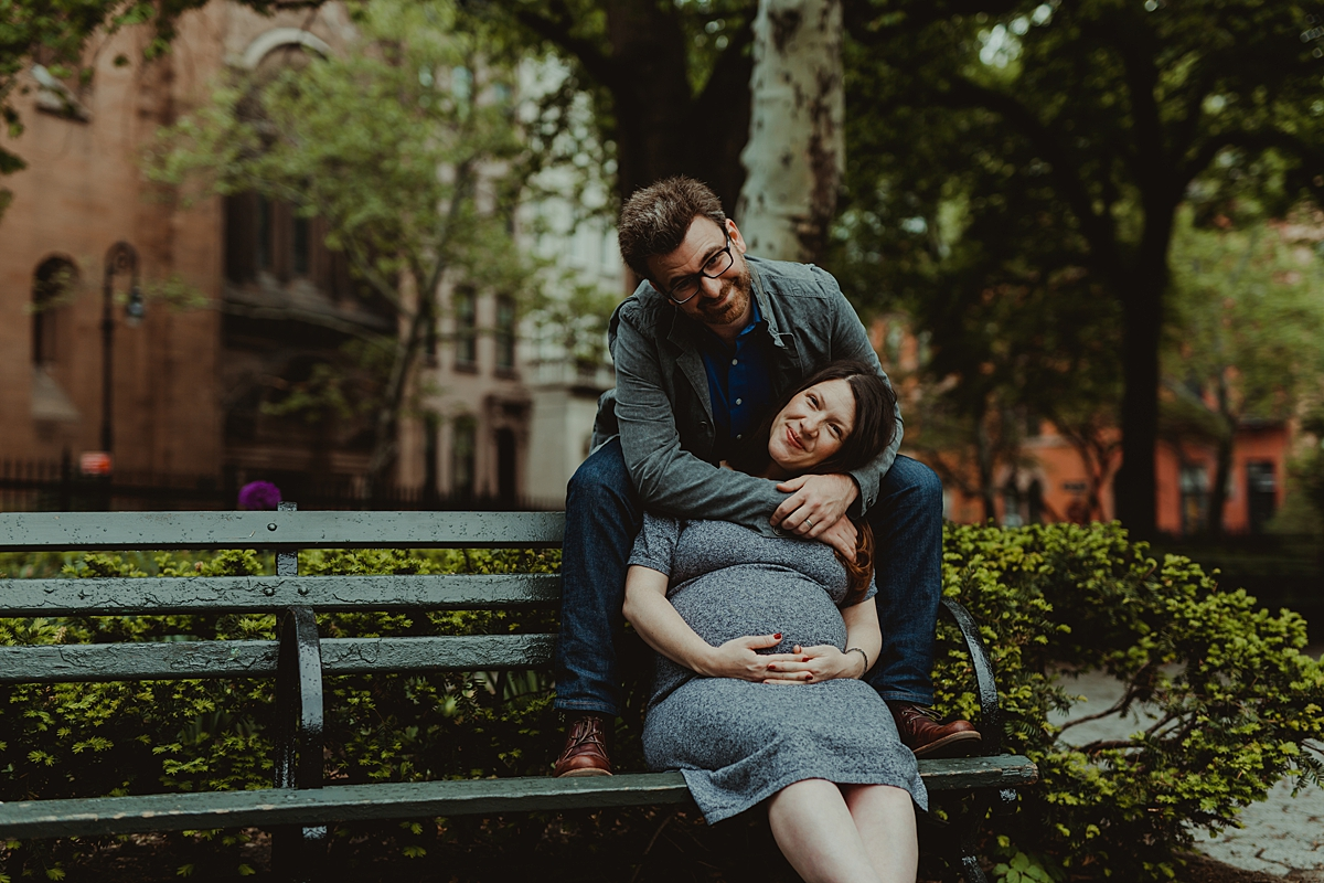 photo of expecting husband and wife sitting on park bench in stuyvesant square during maternity photo session in nyc. photo by nyc family and newborn photographer krystil mcdowall