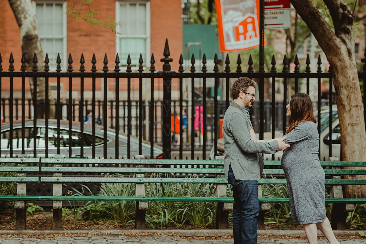candid photo of pregnant husband and wife in stuyvesant square park during their nyc maternity photo session. photo by nyc family and newborn photographer krystil mcdowall