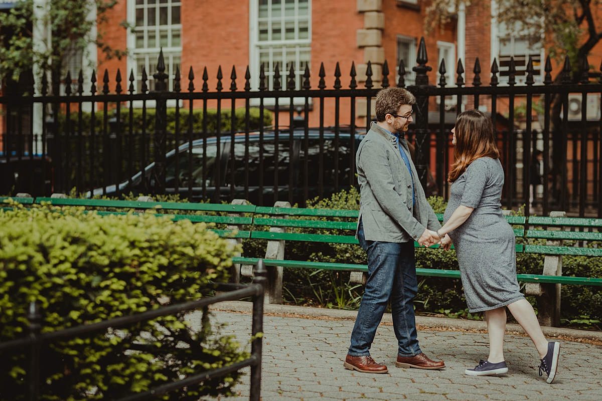 image of husband and wife in the park and holding hands looking into each other's eyes during their nyc maternity photo session. photo by nyc family and newborn photographer krystil mcdowall